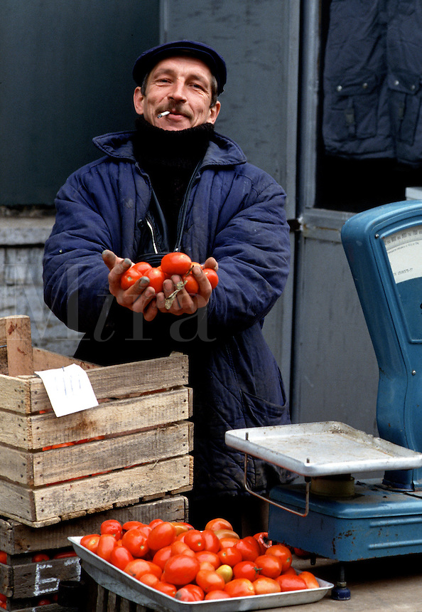 A Russian produce vendor and farmer offers tomatoes for sale at an outdoor market. Moscow, Russia.