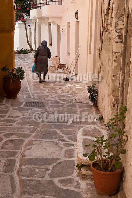 Old woman with cane walks a narrow street, Naoussa, Greece.