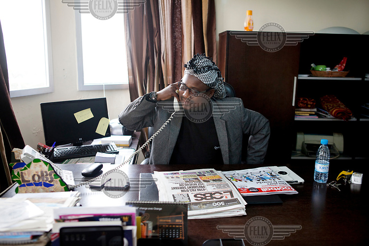 Director of Publications of L'Observateur, Alioune Badara Fall, speaks on the phone in his office.