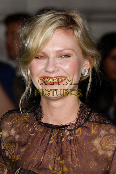 Kirsten Dunst (wearing new fashion label Honor's spring 2012 collection).UK Premiere of 'Melancholia' at the Curzon, Mayfair, London, England..September 28th 2011.headshot portrait organza paisley printed gold woven weave sheer black brown smiling lipstick teeth.CAP/AH.©Adam Houghton/Capital Pictures.