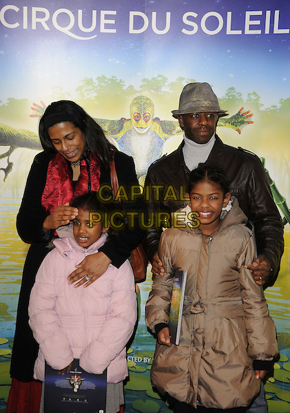 Adrian Lester & family.'Cirque Du Soleil: Totem' UK Premiere, Royal Albert Hall, London, England..5th January 2012.half length black pink brown jacket coat kids children red .CAP/CAN.©Can Nguyen/Capital Pictures.