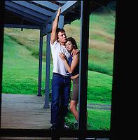 Couple standing on porch embracing seen through screen door<br />