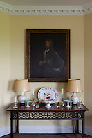 A dark early 18th century family portrait hangs on a wall of the drawing room