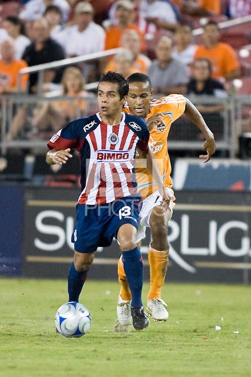 CD Guadalajara forward Sergio Avila (13) dribbles away from Houston Dynamo midfielder Ricardo Clark (13) during the group stage of the Superliga 2008 tournament at Robertson Stadium in Houston, TX on July 15, 2008.