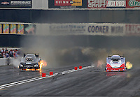 Feb 7, 2015; Pomona, CA, USA; NHRA funny car driver Jeff Arend (left) blows an engine on fire alongside Robert Hight during qualifying for the Winternationals at Auto Club Raceway at Pomona. Mandatory Credit: Mark J. Rebilas-USA TODAY Sports