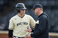 Wake Forest Demon Deacons assistant coach Bill Cilento (right) chats with Brendan Tinsman (9) during the game against the Notre Dame Fighting Irish at David F. Couch Ballpark on March 10, 2019 in  Winston-Salem, North Carolina. The Demon Deacons defeated the Fighting Irish 7-4 in game one of a double-header.  (Brian Westerholt/Four Seam Images)
