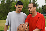 Hispanic father coaching his son in basketball techniques