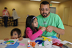 Avani Martinez, 4, center, and her dad Gilbert work on a craft project as little sister Adi, 1, peaks over the table during Nevada Wildflower Family Fun Day at the Nevada State Museum in Carson City Saturday April 11, 2015. The Sparks family  was treated to information, hands-on experiences and crafts.<br />