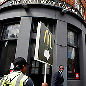 "London, Great Britain, July 2010:.Man holding a sign showing way to the nearest McDonald's, by the recently closed  ""The Railway Tavern"" pub in Hackney..(Photo by Piotr Malecki / Napo Images)..Londyn, Wielka Brytania, Lipiec 2010:.Mezczyzna trzyma znak pokazujacy droge do najblizszego Mc Donaldsa, przed zamknietym pubem ""The Railway Tavern"" w dzielnicy Hackney.. Fot: Piotr Malecki / Napo Images"