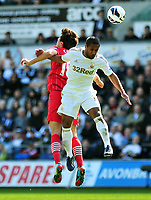 Pictured: Swansea's Wayne Routledge (R) winning the header.<br />