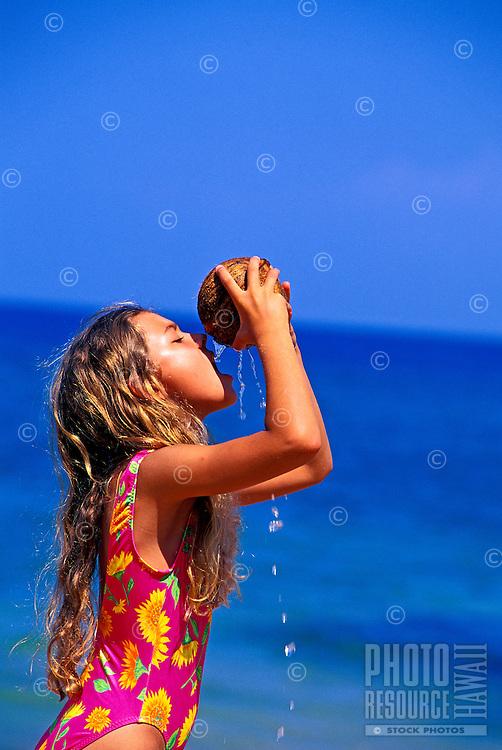 Girl drinking from coconut. Ulua Beach, Wailea, Maui