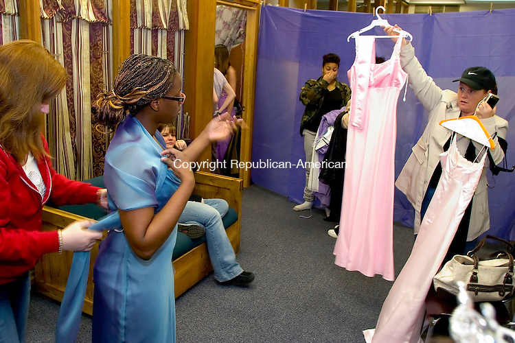 WATERBURY, CT- 15 APRIL 07- 041507JT13- <br /> Dawn Venditti, right, shows Shenise Smith, 18, a selection of dresses as Natalie Testa, left, from Ragtime Boutique in Watertown, adjusts Smith's shawl at the Waterbury Youth Services' fourth annual Perfect Prom Project on Sunday at the agency. Gowns for the event were donated by Joyce's Bridal &amp; Formal Wear, Delianne Bridal &amp; Formal Wear, Great White Way, Ragtime Boutique, and Wedding Embassy among other private donors. Also featured were makeup demonstrations by Mary Kay representative Shauna Bowers, jewelry donated by Heather Jones, and flower arrangements donated by O'Rourke and Birch Florist.<br /> Josalee Thrift Republican-American