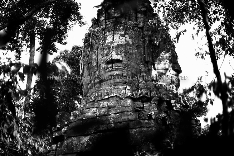 4/20/2003--Angkor Wat Temples, Siem Reap, Cambodia ..North Gate of TA PHROM.  .Ta Prohm is locating southwest of the East Mebon and east of Angkor Thom. Its outer enclosure is near the corner of Banteay Kdei. It was built about mid-12th century to early 13th century (1186) by the King Jayavarman VII, dedicated to the mother of the king (Buddhist) replica to Bayon style of art. ..BACKGROUND ..Ta Prohm is the undisputed capital of the kingdom of the Trees. It has been left untouched by archaeologists except for the clearing of a path for visitors and structural strengthening to stave of further deterioration. Because of its natural state, it is possible to experience at this temple the wonder of the early explorers when they came upon these monuments in the middle of the nineteenth century. .Shrouded in dense jungle the temple of Ta Prohm is ethereal in aspect and conjures up a romantic aura. Fig, banyan and kapok trees spread their gigantic roots over stones, probing walls and terraces apart, as their branches and leaves intertwine to form a roof over the structures. Trunks of trees twist amongst stone pillars. The strange, haunted charm of the place entwines itself about you as you go, as inescapably as the roots have wound themselves about the walls and towers', wrote a visitor 40 years ago. ..A Sanskrit inscription on stone, still in place, give details of the temple. Ta Prohm 3,140 villages. It took 79,365 people to maintain the temple including 18 great priests, 2,740 officials, 2,202 assistants and 615 dancers. Among the property belonging to the temple was a set of golden dishes weighing more than 500 kilograms, 35 diamonds, 40,620 pearls, 4,540 precious stones, 876 veils from China, 512 silk beds and 523 parasols. Even considering that these numbers were probably exaggerated to glorify the king, Ta Prohm must have been an important and impressive monument. ..All photographs ©2003 Stuart Isett.All rights reserved.