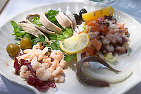 A salad dish with seafood, anchovies, shrimps, calamares calamari, olives ... Hotel and restaurant Kompas. Uvala Sumartin bay between Babin Kuk and Lapad peninsulas. Dubrovnik, new city. Dalmatian Coast, Croatia, Europe.