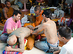 Nakorn Chai Sri, Thailand, March 2, 2012, Wat Bang Phra Buddhist Monk gives a devotee a sak yant magical tattoo.