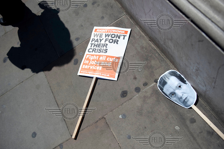 Discarded placards after a demonstration against the public spending cuts imposed by the government in the Budget, near the Houses of Parliament in Westminster, London.