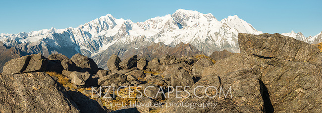 Afternoon light on rocks with views of Southern Alps with highest peaks Aoraki Mount Cook, Mount Tasman and La Perouse, Westland Tai Poutini National Park, UNESCO World Heritage Area, West Coast, New Zealand, NZ