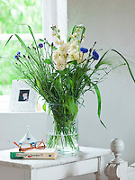 A bouquet of blue and white meadow flowers brings nature into the bedroom