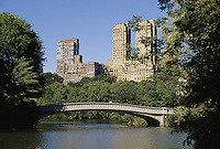 New York City, NY.The buildings of Central Park West seen from Central Park. In foreground the Bow bridge spans a neck of Central Park Lake