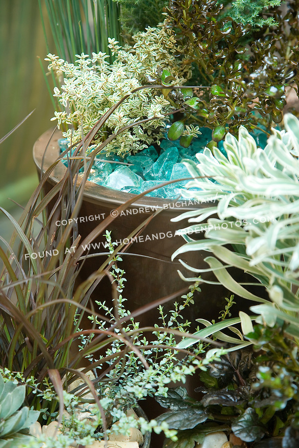 In this blue-green motif, aqua-colored tumbled glass mimics the colors of, among others, silver thyme (rear copper pot, left side), and Euphorbia 'Glacier Blue' (right middle).