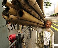 A man carries bamboo scaffolding in Hong Kong.