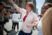 NYC Mayoral candidate and City Council Speaker Christine Quinn joins thousands of Dominican-Americans and their friends and supporters as she campaigns in the Dominican Day Parade in New York on Sixth Avenue on Sunday, August 11, 2013.  Politicians, flags and cultural pride were on display at the annual event. Quinn's poll numbers are at 25 percent placing her first in the field of Democratic candidates for New York mayor but 40 percent of the votes are required to avoid a run-off election. The primary election is approximately one month away. (© Richard B. Levine)