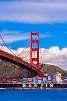 Container ship sailing through San Francisco Bay crossing under the Golden Gate Bridge, San Francisco, California USA