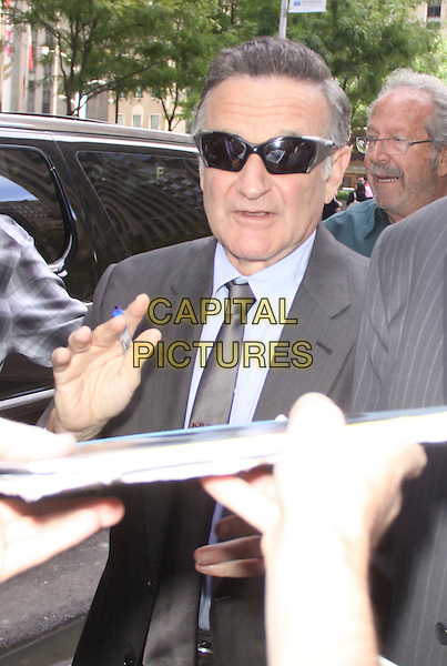 Robin Williams<br /> At SiriusXM Studios in New York City, New York, USA.<br /> September 25th, 2013 <br /> half fan signing autographs length sunglasses shades grey gray suit<br /> CAP/MPC/RW<br /> &copy;RW/ MediaPunch/Capital Pictures