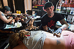 Garden City, New York, USA. September 13, 2015. R-L, JASON ACKERMAN and TROY RADECKI, a pro team of tattoo artists, are tattooing two young woman, lying prone, at the United Ink Flight 915 Tattoo convention at the Cradle of Aviation Museum in Long Island.