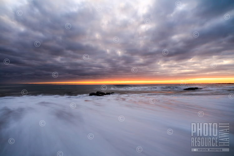 The horizon glows with first light as clouds line the sky and waves rush ashore at Kealia Beach Park, Kapa'a, Kaua'i.