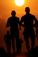 Dark silhouettes of runners against a searing hot sun at the annual Ironman Triatholon on the Big Island of Hawaii.