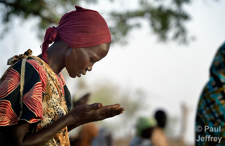 A displaced Catholic woman prays during an open air mass in Agok, a town in the contested Abyei region where tens of thousands of people fled in 2011 after an attack by soldiers and militias from the northern Republic of Sudan on most parts of Abyei. Although the 2005 Comprehensive Peace Agreement called for residents of Abyei--which sits on the border between Sudan and South Sudan--to hold a referendum on whether they wanted to align with the north or the newly independent South Sudan, the government in Khartoum and northern-backed Misseriya nomads, excluded from voting as they only live part of the year in Abyei, blocked the vote and attacked the majority Dinka Ngok population. The African Union has proposed a new peace plan, including a referendum to be held in October 2013, but it has been rejected by the Misseriya and Khartoum. The Catholic parish of Abyei, with support from Caritas South Sudan and other international church partners, has maintained its pastoral presence among the displaced and assisted them with food, shelter, and other relief supplies. Yet in Agok they have no church building, so Mass and religious instruction is carried out in the open air.