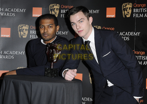 NOEL CLARKE & NICHOLAS HOULT.The Orange Rising Star Award Nominations, BAFTA HQ, Piccadilly, London, England..January 12th, 2010.half length blue black jumper top suit jacket white table leaning award trophy.CAP/CAN.©Can Nguyen/Capital Pictures.