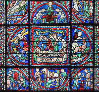Above, Jacob blessing Ephraim and Manasseh, crossing his arms over so as to give the birthright to Ephraim the youngest son, on the right. In the middle, Samson carrying the gates of Gaza, the anointing and entombment of Christ and David fighting with a lion. Below, donor windows of the blacksmiths and farriers; men throwing fuel into a forge, a farrier fitting a horseshoe while 2 men hold the horse and 2 blacksmiths beating a red hot piece of iron on an anvil, quatrefoil from the Typological Passion stained glass window, 1210-25, in the transept of Chartres Cathedral, Eure-et-Loir, France. This window, unusually, reads from top to bottom. Chartres cathedral was built 1194-1250 and is a fine example of Gothic architecture. Most of its windows date from 1205-40 although a few earlier 12th century examples are also intact. It was declared a UNESCO World Heritage Site in 1979. Picture by Manuel Cohen