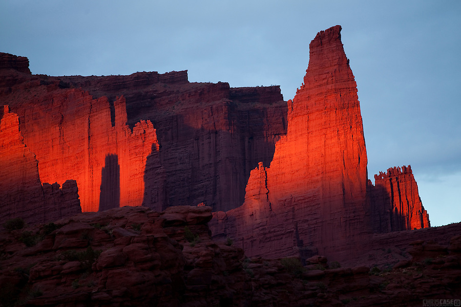 Fisher Towers glow in the light of a classic Utah sunset. <br /> <br /> The towers are a series of spires made of Cutler sandstone capped with Moenkopi sandstone and caked with a stucco of red mud located near Moab, Utah. They are named for a miner who lived near them in the 1880s. <br /> <br /> The tower is world renowned as a subject for photography and for its classic rock climbing routes.