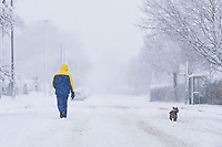 A man walks his dog in the snow in the village of Redbourn, Hertfordshire, UK. Sunday 10 December 2017.