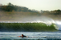 A local surfer paddles out to the surf in Tamarindo Costa Rica.