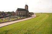 Kerkje van Wierum met begraafplaats, vlak langs de Waddenzeedijk.  Small church of Wierum with   , close to the seawall along the Wadden Sea.