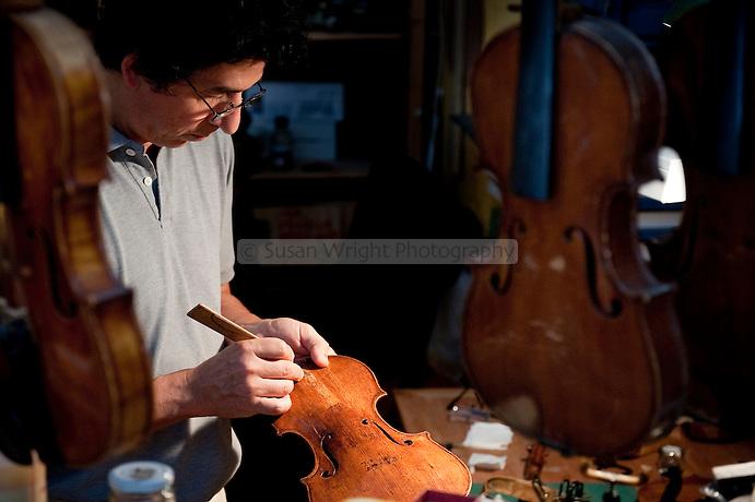 Aldo Santini, artisan violin maker and restorer (liutaio) delicately repairing a 17th century violin in his workshop (bottega) on Via dei Velluti in Florence, Italy