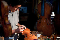 Aldo Santini, artisan violin maker and restorer (liutaio) delicately repairing a 17th century violin in his workshop (bottega) on Via dei Velluti in Florence, Italy
