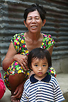 A woman and child, both former river dwellers, sit for a portrait in Hue, Vietnam. The woman and little girl are beneficiaries of a project by the non-governmental organization Hearts for Hue to relocate river dwellers into permanent housing. April 22, 2013.