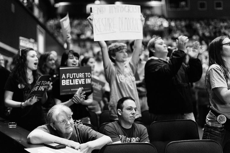 March 11, 2016. Raleigh, North Carolina.<br />  Alcinda Moore, lower left, looked on as Sanders took the stage.<br />  Democratic presidential candidate Bernie Sanders held a rally at Raleigh's Memorial Auditorium days before the North Carolina primary. Although behind in the polls to Hillary Clinton, thousands of supporters showed up for the rally with hundreds forced to wait outside.