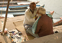 Barber shaving beard of old man on the ghats of River Ganges in Varanasi. (Photo by Matt Considine - Images of Asia Collection)