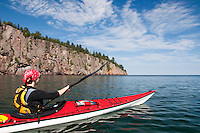 Sea kayaker on Lake Superior with Shovel Point along Minnesota North Shore at Tettegouche State Park.
