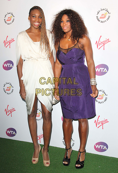 Venus Williams and Serena Williams.Richard Branson's Pre-Wimbledon Party at Kensington Roof Gardens, London, England, UK, June 21st 2012..full length dress  plaits bleached blonde hair braids smiling white cream peep toe shoes  purple sisters family siblings .CAP/ROS.©Steve Ross/Capital Pictures