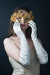 Portrait of a teenager wearing a masquerade mask standing against a black backdrop wearing white gloves adjusting golden mask