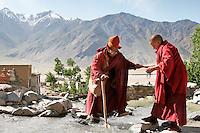 Une none aide un vieux moine gelukpa à traverser le torrent qui traverse inopinément le village de Karsha à l'entrée de la vallée du Zanskar. Ladakh Himalaya Inde. Photo : Vibert / Actionreporter.com