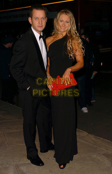 ALI BASTIAN.RTS Programme Awards (Royal Television Society), Grosvenor House Hotel, Park Lane, London, England, UK..March 14th 2006.Ref: CAN.full length black suit tuxedo red clutch purse dress.www.capitalpictures.com.sales@capitalpictures.com.©Capital Pictures