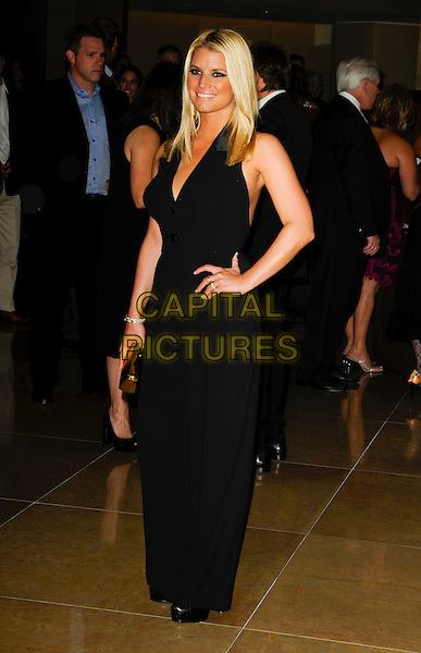 JESSICA SIMPSON.arriving at Operation Smile at the Beverly Hilton Hotel in Beverly Hills, California, USA, October 2nd 2009..full length halterneck black jumpsuit catsuit hand on hip buttons gold clutch bag .CAP/ROT.©Lee Roth/Capital Pictures.