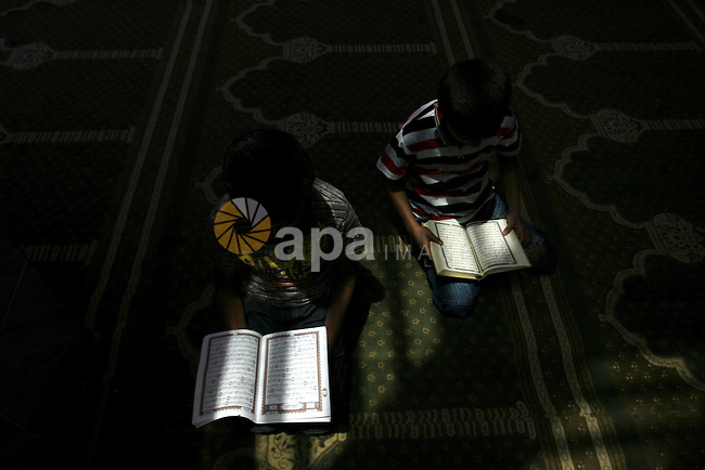 Palestinian boys read verses from the Quran during a class on how to read Islam's holy book, at a mosque in Rafah, southern Gaza city, on June 14, 2012. A summer camp in the Gaza Strip, 'Crown of Dignity IV', plans to teach 2,500 students about the Quran during the summer months inside mosques throughout the Gaza Strip.  Photo by Eyad Al Baba